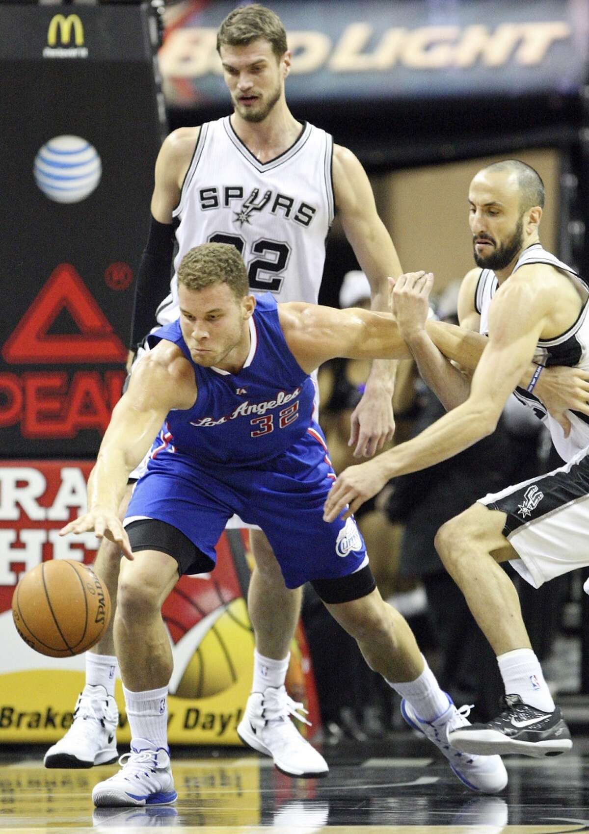 Los Angeles Clippers' Blake Griffin and San Antonio Spurs' Manu Ginobili grab for a loose ball as San Antonio Spurs' Tiago Splitter looks on during first half action Monday Dec. 22, 2014 at the AT&T Center.