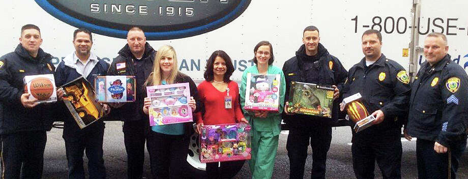 Police officers deliver truckloads of toys Monday to nurses at Bridgeport Hospital. The toys were collected through the Police Department-sponsored program from residents' donations over the last several weeks. Photo: Contributed Photo / Fairfield Citizen