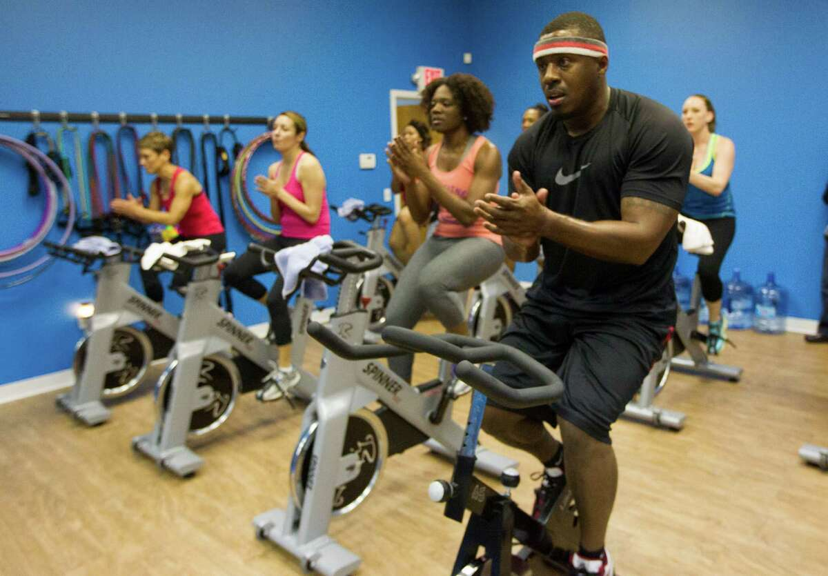 Chris Boykin, front, leads one of his signature spin/hula-hoop classes at Glory Fitness.