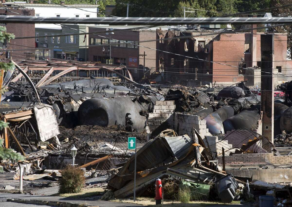 The downtown core lies in ruins Thursday, July 11, 2013 in Lac-Megantic, Quebec, Canada. The first victim of a runaway oil train's explosive derailment in the Quebec town was identified Thursday, more than five days since the disaster, which left behind a scorched scene so dangerous that it slowed the search for 50 people presumed dead. (AP Photo/Ryan Remiorz, The Canadian Press)