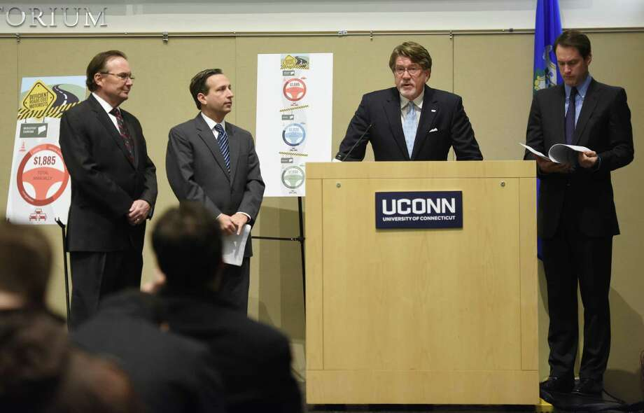 TRIP Executive Director Will Wilkins speaks at the podium beside Stamford Chamber of Commerce President Jack Condlin, far left, State Sen. Bill Duff, second from left, and U.S. Rep. Jim Himes, right, at the University of Connecticut Stamford Branch in Stamford, Conn. Tuesday, Dec. 23, 2014.  A new report by national transportation research group TRIP highlights the urgent need for long-term transportation investments.  The report finds that the average Bridgeport-Stamford area driver loses nearly $1,900 each year as a result of driving on roads that are congested, deteriorated or lack some desirable safety features. Photo: Tyler Sizemore / Greenwich Time