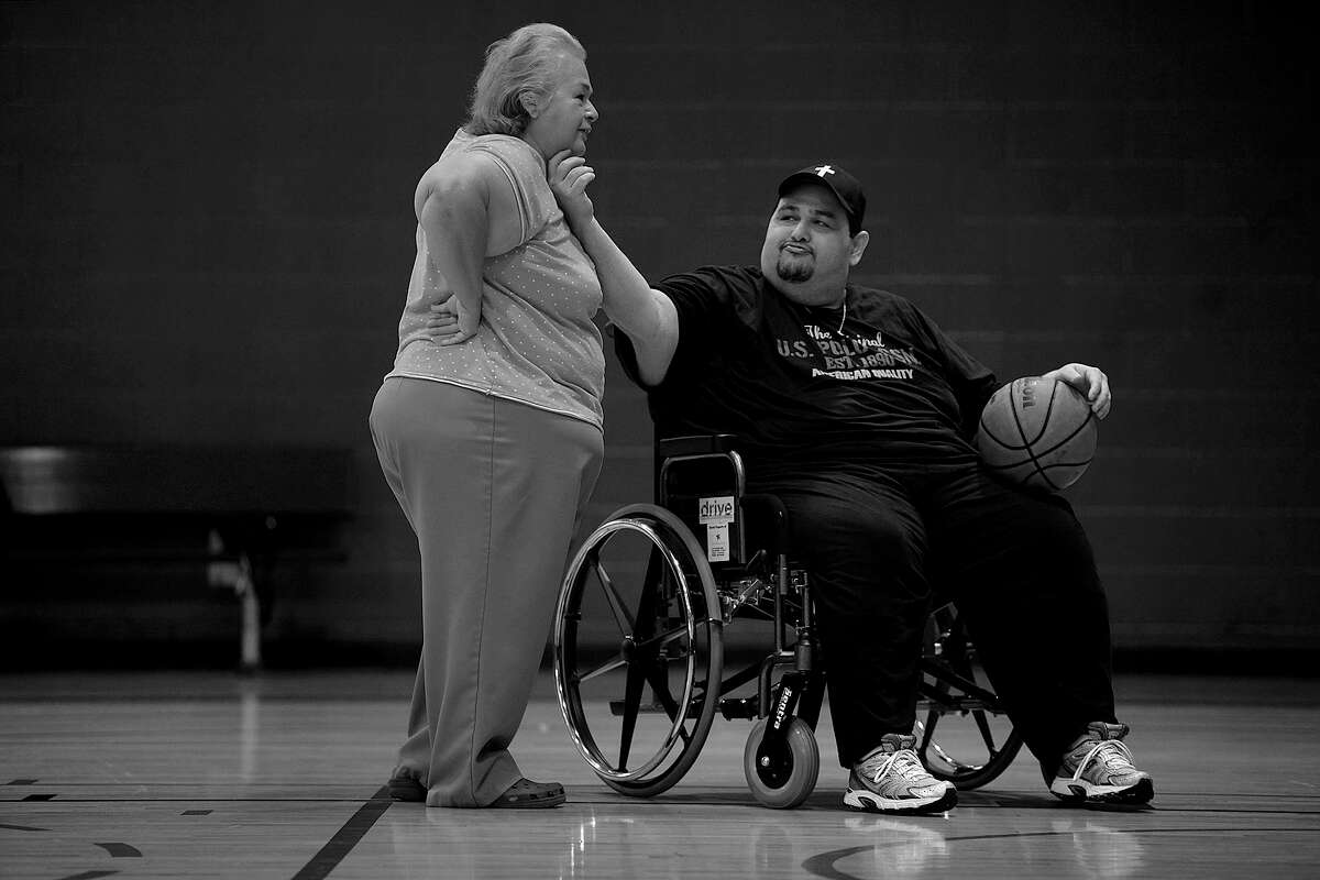Garcia teases his mother and caretaker, Elena Garcia, as he shoots baskets at the Westside Family YMCA in September 2011. When Garcia began going to the YMCA, he was only able to walk in the pool. As he lost weight and became more mobile, he could eventually lift weights.