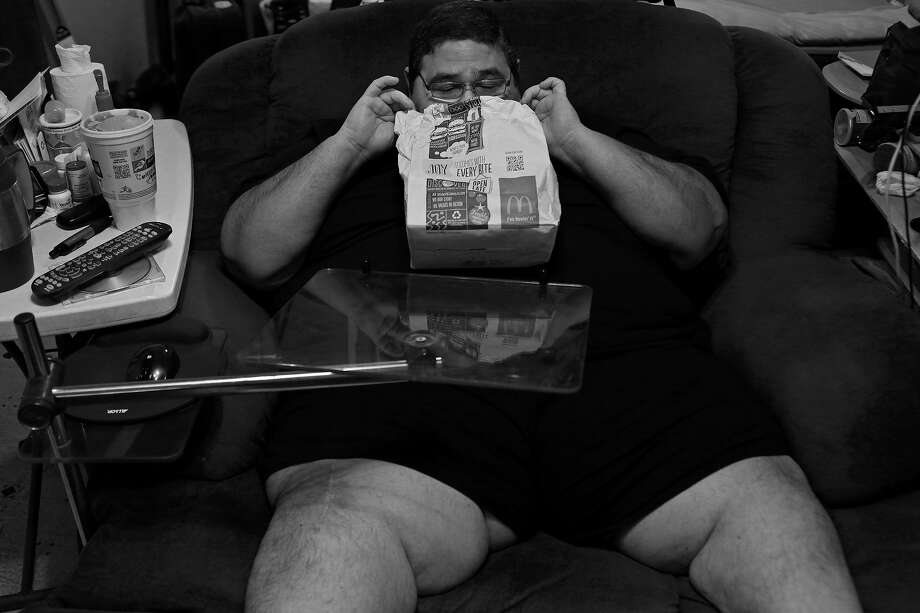 "Confined to his chair and house again, Garcia peeks into a bag holding a 20-piece box of Chicken McNuggets brought to him by his mother in September. Mondays were always ""cheat days"" while dieting, but in recent months Garcia admitted that most days had become cheat days as his motivation to lose weight dwindled. Photo: Lisa Krantz /San Antonio Express-News / San Antonio Express-News"