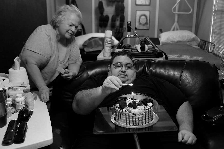 Garcia lights the candle on his cake for his 49th birthday Nov. 19, as his mother, Elena Garcia, begins to sing to him at their home in San Antonio. Photo: Lisa Krantz / San Antonio Express-News / San Antonio Express-News