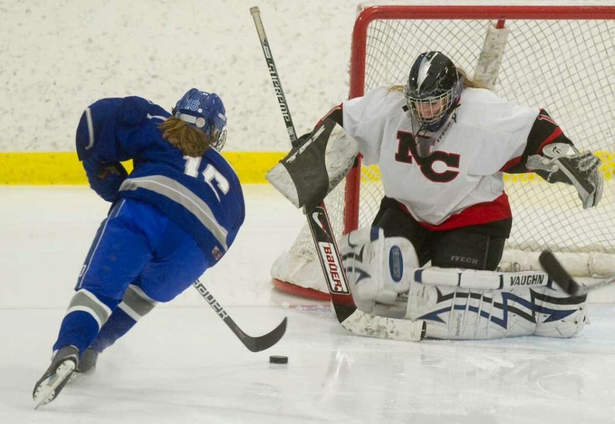 New Canaan's Charlotte Sptizfaden, right, gets ready to make a save as Darien's Emily Tropsa, left, takes a shot during the FCIAC girls hockey championship at Terry Conners Rink in Stamford, Conn. on Saturday, Feb. 27, 2010.