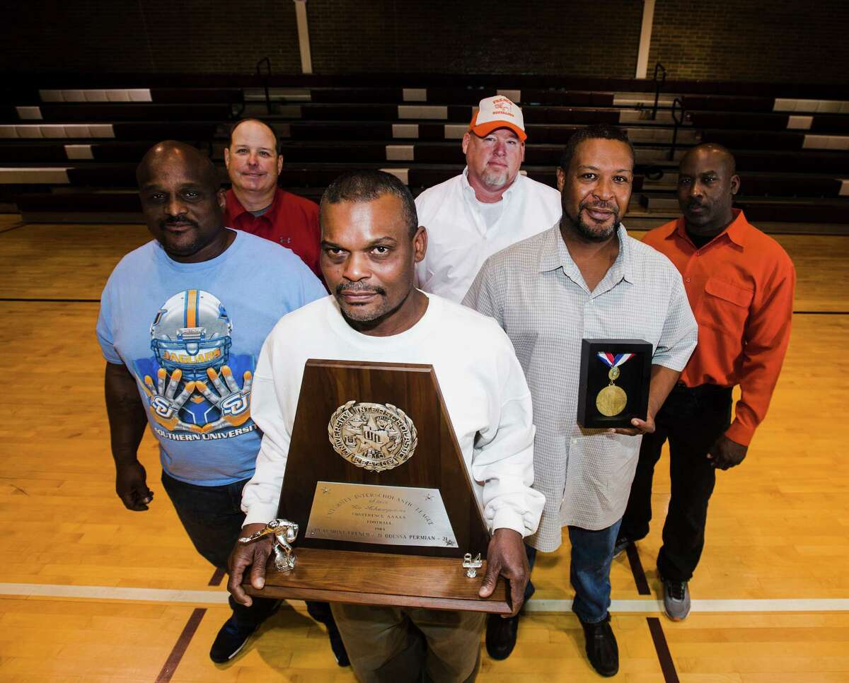 Members of the 1984 Beaumont French football team -- clockwise from front: Paul Jones, Thad Nobles, Kevin Haskett, Barry Edelmon, Jeff Turner, and Jeff Truss, Jr. -- It was 30 years ago that Beaumont French tied Odessa Permian 21-21 and claimed their portion of a state championship title. Team members gathered to reminisce about the game and their lives since. Photo taken Wednesday 12/17/14 Jake Daniels/The Enterprise