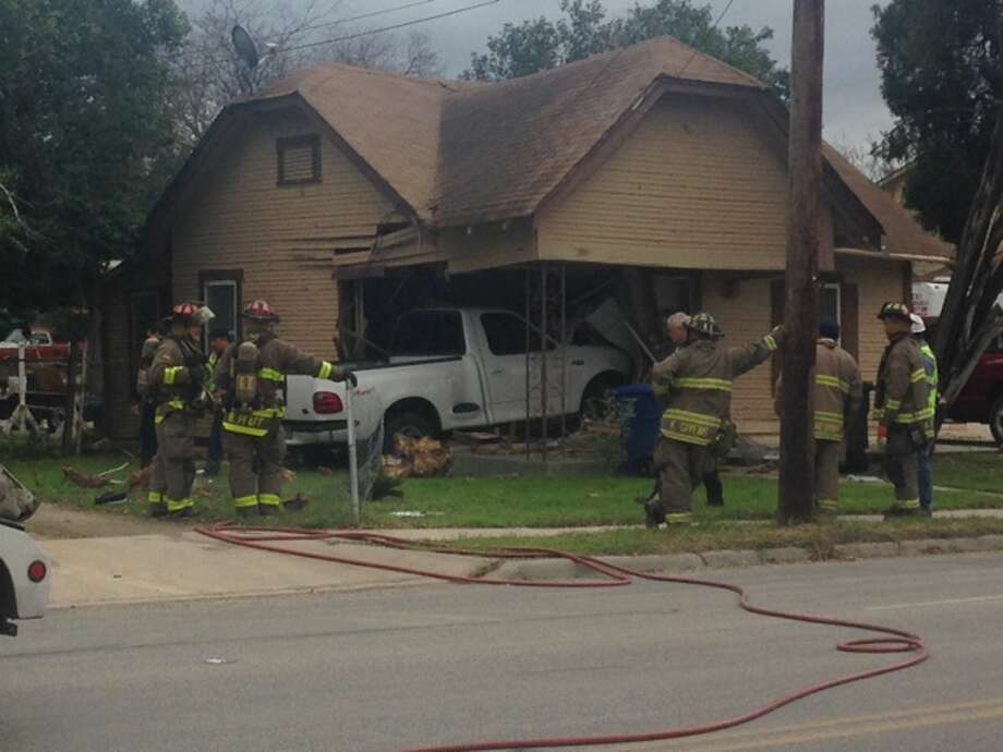 A woman and a young boy were injured Tuesday afternoon when a pickup truck slammed into their home on the West Side. Photo: By Mark D. Wilson/San Antonio Express-News