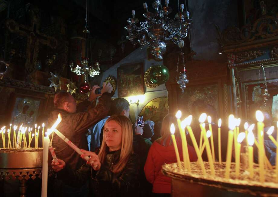 Christian worshipers light candles inside the Church of the Nativity, believed to be the birthplace of Jesus Christ, in the West Bank biblical town of Bethlehem. City traffic is a mess year-round. Photo: MUSA AL-SHAER / AFP/Getty Images / AFP