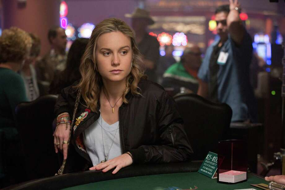 """At left: Mark Wahlberg (left) plays an Ivy League professor of literature who owes money to a mobster (John Goodman) in """"The Gambler."""" Above: Brie Larson plays a student that the professor is involved with. Photo: Claire Folger / Associated Press / Paramount Pictures"""