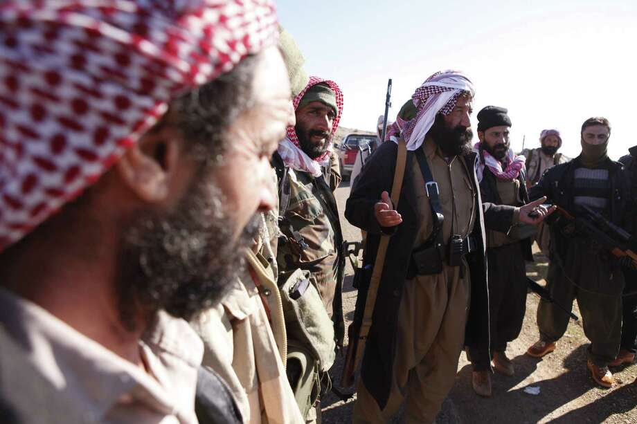 """Yazidi fighters gather on Mount Sinjar as they head to battle Islamic State militants, in Iraq. Hundreds of Yazidi women and girls were captured by the militants, and turned into sex slaves or forcibly """"married."""" Photo: Dalton Bennett / Associated Press / AP"""