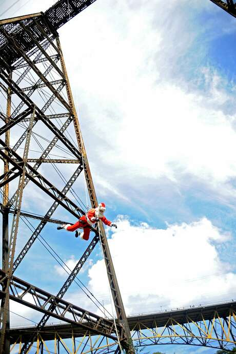 Firefighter Hector Chacon, dressed as Santa, goes down a cable from a bridge to deliver presents to children in Guatemala City. Photo: Johan Ordonez, AFP/Getty Images