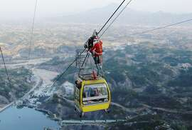 In this Saturday, Dec. 20, 2014 photo, a worker dressed as a Santa Claus descends on the cable to deliver gifts to tourists in the cable car ahead of Christmas Day celebrations at a scenic zone in Pingjiang county in south China's Hunan province. (AP Photo) CHINA OUT