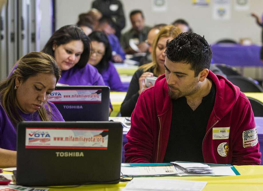 """In this Monday, March 31, 2014 file photo, SEIU-UHW worker Kathy Santana, left, assists Ruben Torres, 27, during a health care enrollment event at the SEIU-UHW office in Commerce, Calif. Millions more Americans signed up to be covered under President Barack Obama's health care initiative, but controversy about """"Obamacare"""" raged on. Criticism from Republicans in Congress was relentless, many GOP-governed states balked at participation, and opinion polls suggested most Americans remained skeptical about the program. (AP Photo/Ringo H.W. Chiu, File) Photo: Ringo H.W. Chiu, Associated Press"""