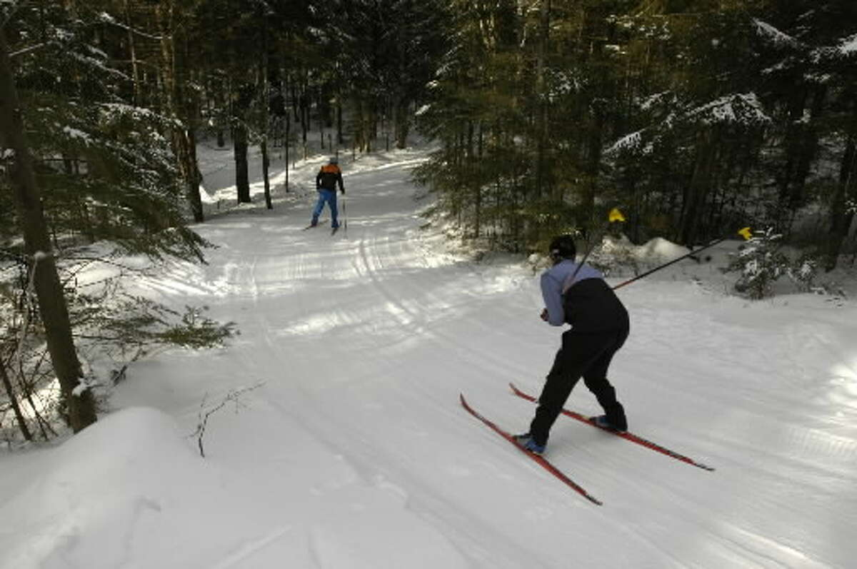 Two skiers head down a trail at Lapland Lake Cross Country Ski and Vacation Center outside Northville in 2005. (Paul Buckowski / Times Union)