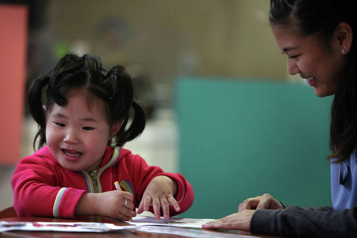 Nomin Gan-Erdene, 4, sits with volunteer Shannel Vidallon at UCSF Benioff Children's Hospital Oakland on Dec. 15. Children's Hospital Oakland is one of a few facilities in the world participating in a clinical trial for neurodegeneration with brain iron accumulation.
