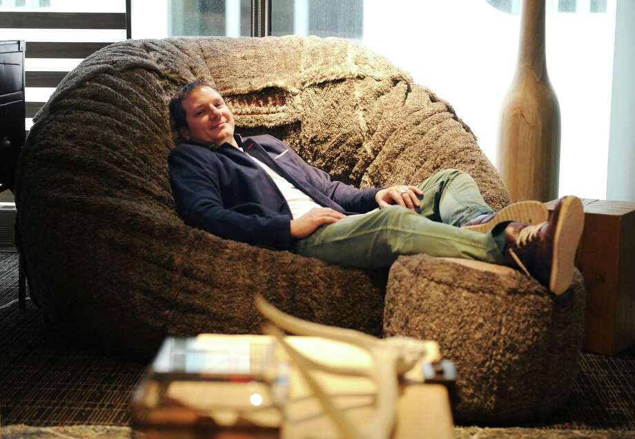 """Lovesac founder Shawn Nelson lounges in a Lovesac at the new Lovesac Headquarters at 2 Landmark Square in downtown Stamford, Conn. Tuesday, Dec. 23, 2014.  Lovesac and its team of about 50 employees moved from the undersized office on Canal Street the new, spacious Landmark Square location about a month ago.  The new office and showroom incorporates Lovesac's """"sactional"""" modular furniture for employees' work spaces. Photo: Tyler Sizemore / Greenwich Time"""