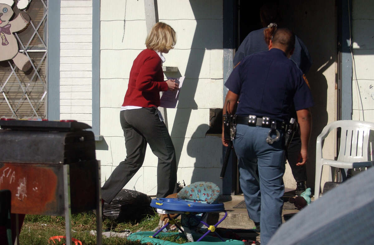 In theis file photo, a Child Protective Services investigative caseworker enters a home to remove a child. Tunrover is high among CPS workers, and releasing exit interviews would provide insight to the problems.