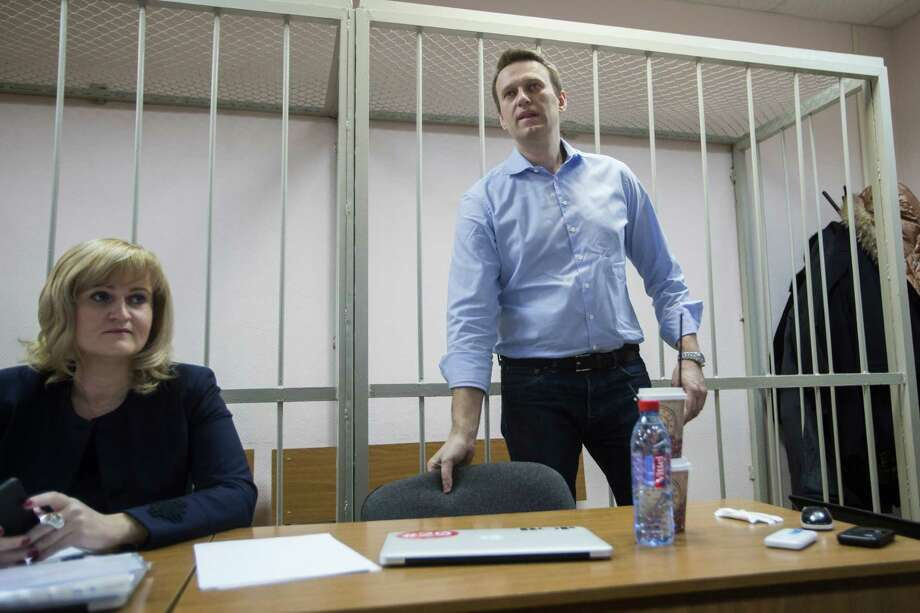Russian opposition activist and anti-corruption crusader Alexey Navalny, right, waits for a start of a trial in a courtroom in Moscow, Russia, Friday, Dec. 19, 2014. Navalny, who has been under house arrest since February, is being charged in a second trial that may put him behind bars for good. (AP Photo/Pavel Golovkin) Photo: Pavel Golovkin / Associated Press / AP