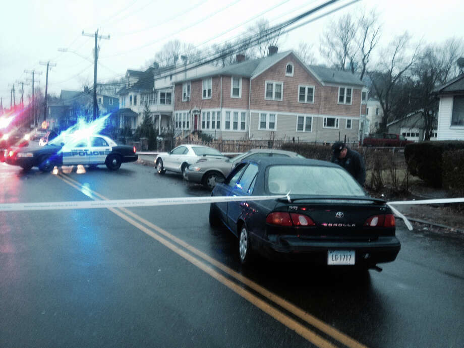 A woman was pinned under parked car on Adams Avenue Tuesday afternoon when a Buick slammed into the rear of the Toyota Corolla which then struck a parked Toyota Camry just as the women was walking past the car. Police said the injured pedestrian under the car was conscious and responsive when she was taken to Stamford Hospital. Photo: John Nickerson / Stamford Advocate