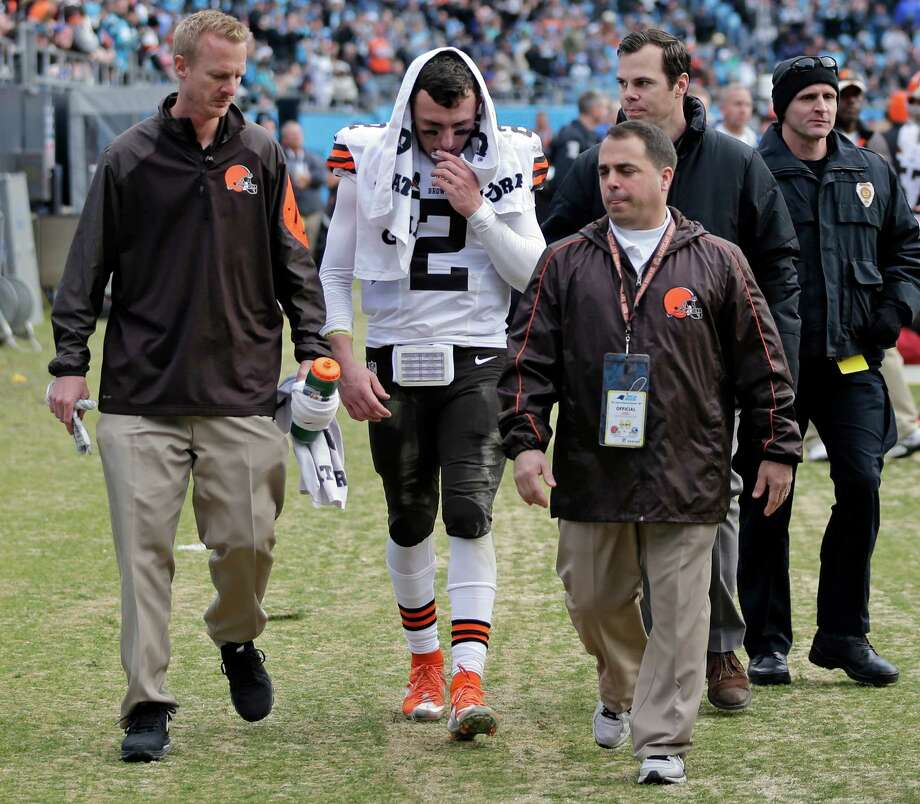 Browns quarterback Johnny Manziel is helped off the field after being injured in the first half of against the Carolina Panthers in Charlotte, N.C. Manziel's rookie season in the NFL wasn't what he or the Browns or his legion of fans expected. He started one game, couldn't make it through his second without getting hurt and didn't look like a franchise-changing quarterback. Photo: Chuck Burton /Associated Press / AP