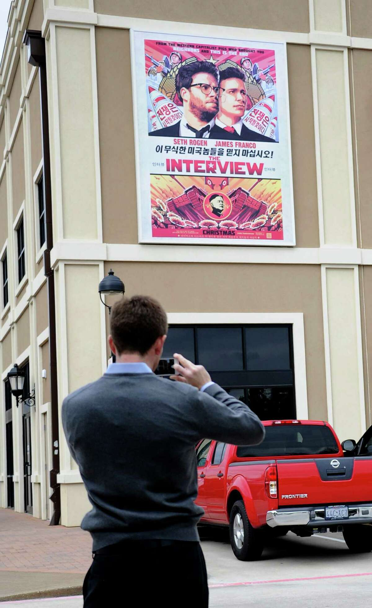 """A man takes a photo of a poster advertising """"The Interview"""" on the back wall of the Alamo Drafthouse Cinema in Houston."""