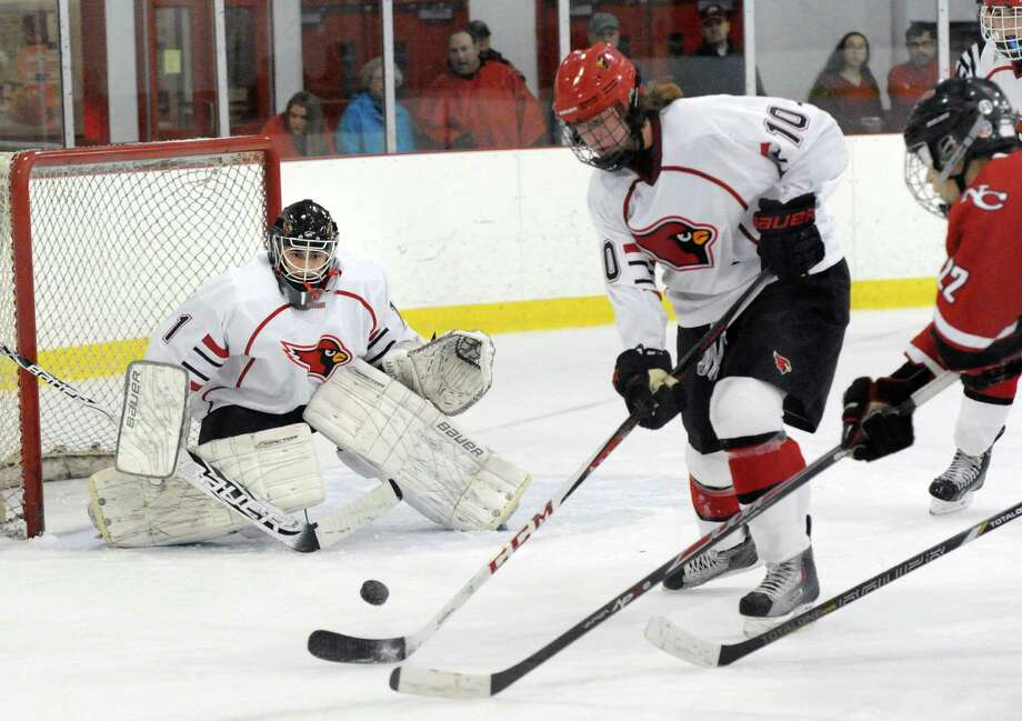 After Greenwich goalie Brian Archino, left, made a stop, Decker Curran (#10) of Greenwich, center, fights to clear the puck as Pat Hompe (#22) of New Canaan attempts to play the rebound during the boys ice hockey game between Greenwich High School and New Canaan High School at Hamill Rink in Greenwich, Conn., Tuesday night, Dec. 23, 2014. Greenwich won 3-2 in overtime on a Brian Silard goal. Photo: Bob Luckey / Greenwich Time