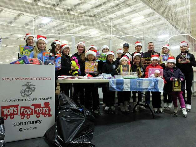 Children with Saratoga Synchronized Skating provided dozens of new, unwrapped toys to officials with the Capital Region Toys for Tots Campaign during a gathering held Dec. 17 at the Saratoga Springs Ice Rink. Receiving the toys on behalf of the campaign were Marine Corps 1st Sgt. Ed Ackley and Navy ET2 Sierra Romleski. (Ryan Lorey) Photo: Picasa