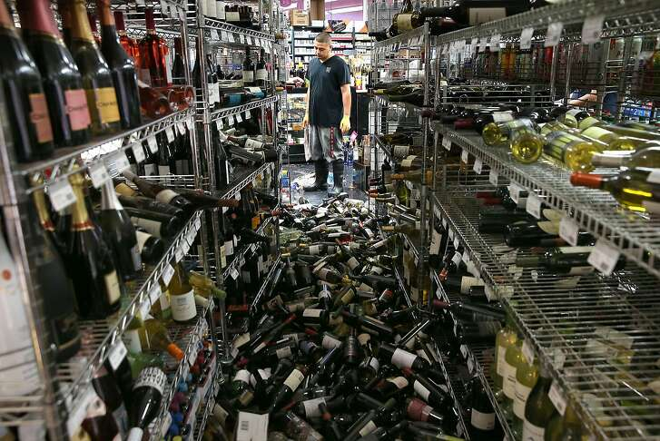NAPA, CA - AUGUST 24:  (ONE OF A 70-PICTURE PACKAGE)   A worker looks at a pile of wine bottles that were thrown from the shelves at Van's Liquors following a reported 6.0 earthquake on August 24, 2014 in Napa, California. A 6.0 earthquake rocked the San Francisco Bay Area shortly after 3:00 am on Sunday morning causing damage to buildings and sending at least 70 people to a hospital with non-life threatening injuries.  (Photo by Justin Sullivan/Getty Images)