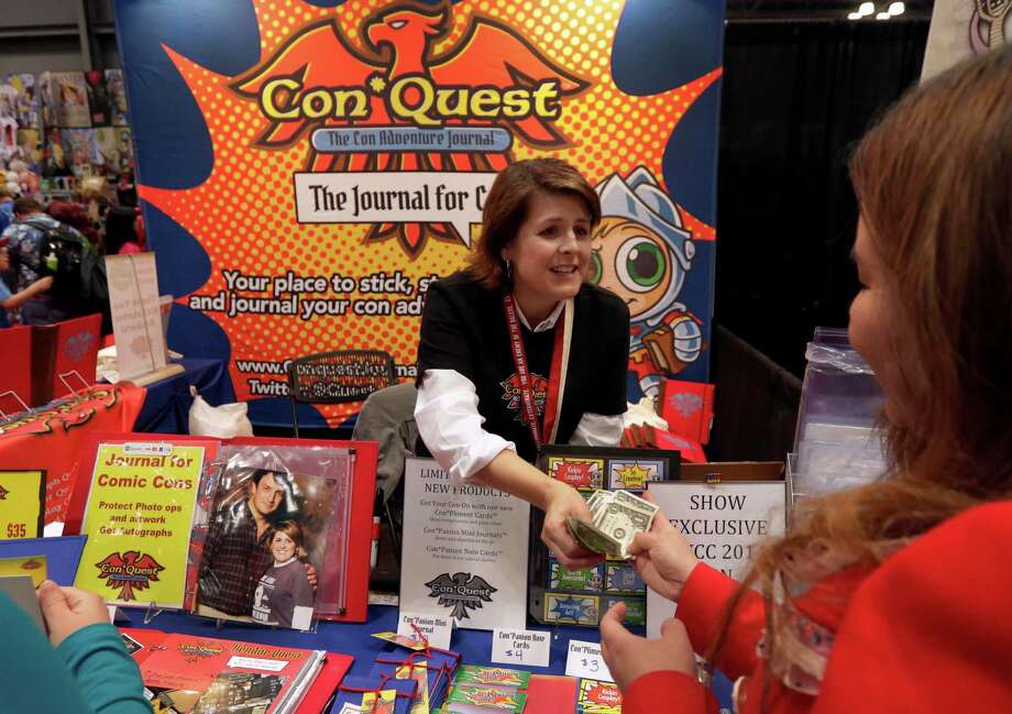 Shelley Harper, from Woodinville, Wash., works at her ConQuest Adventure Journal booth during the first day of New York Comic Con, held this fall. Harper raised nearly $12,000 to make her ConQuest Adventure Journals, a book for Comic Con attendees to store autographs, photos and other mementos, after it was chosen as a Kickstarter Staff Pick. Photo: Richard Drew /Associated Press / AP