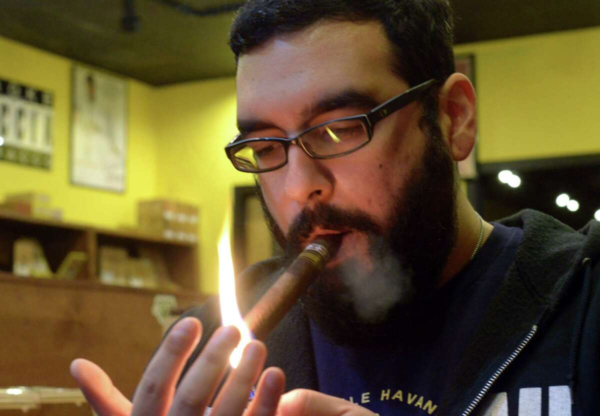 Gabriel Garcia is the owner of Cigar Pointe. He is anticipating a demand for Cuban cigars. He lights up a Tatuaje Cojonu 2003 at his shop on Tuesday, Dec. 23, 2014.