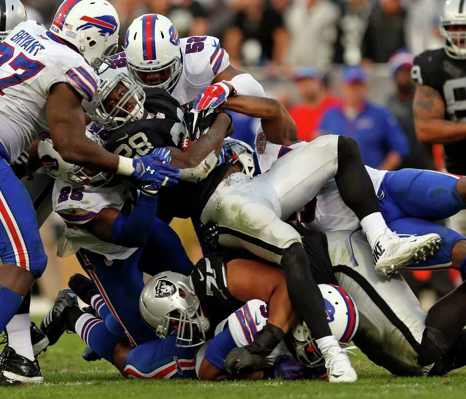 Raiders running back Latavius Murray (center), shown here being gang-tackled in Sunday's win over the Bills, has 376 yards in his past five games, and in two of those he had only four carries. Photo: Scott Strazzante / The Chronicle / ONLINE_YES