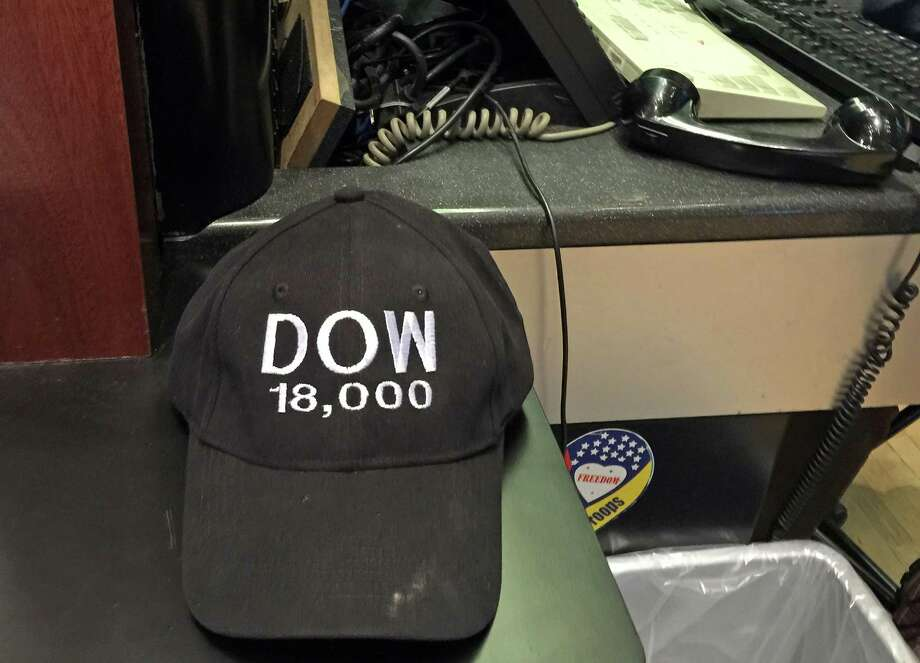 """(FILES) File photo dated December 11, 2014 shows a financial reporter's cap with the Dow Jones projected 18,000 mark stitched upon it at a New York City office. The Dow closed December 23, 2014 above 18,000 for the first time, prolonging a so-called """"Santa Claus"""" rally after a surprisingly strong US economic growth report. At the closing bell, the Dow Jones Industrial Average stood at 18,027.45, up 68.01 points (0.38 percent). AFP PHOTO LUC OLINGA  LUC OLINGA/AFP/Getty Images Photo: LUC OLINGA, Staff / AFP/Getty Images / AFP"""