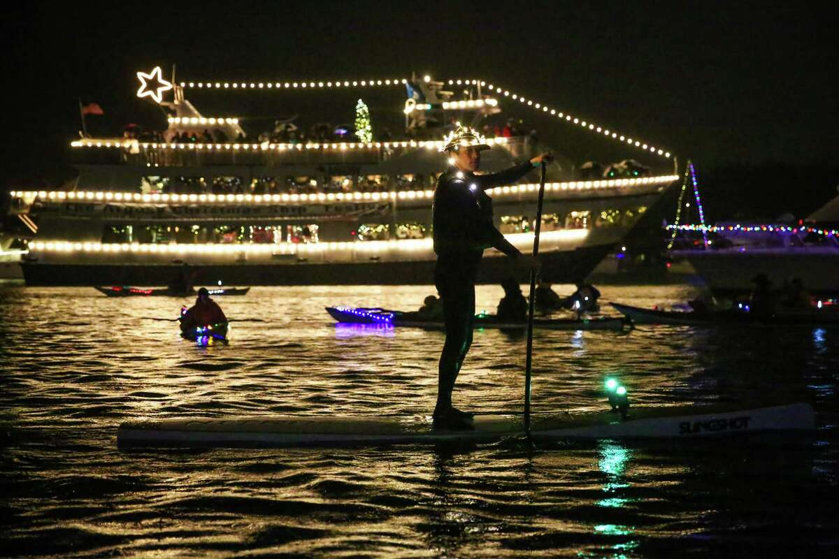 A paddle boarder pushes past during the finale of the Christmas Ships Festival on Lake Union and Portage Bay in Seattle on Tuesday. Despite pouring rain, the festival brought out hundreds of boats and thousands of spectators. Since 1949, the event has sailed to different Puget Sound waterfront communities, bringing music and decorated boats.
