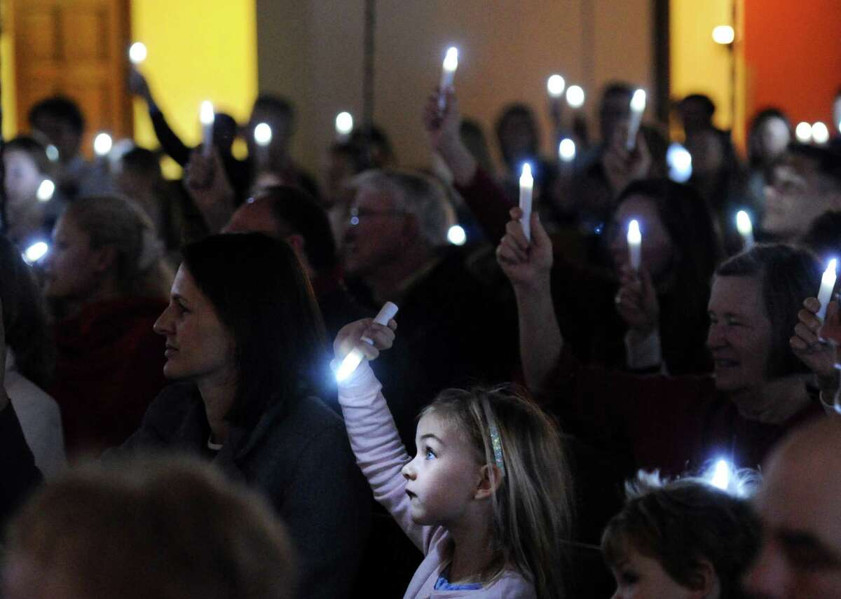 Carla Schrader, 5, holds up an electric candle during the Children's Christmas Eve service at the First Congregational Church in Old Greenwich, Conn., Wednesday, Dec. 24, 2014. The service featured a Nativity Pageant, a performance by the Cherub Choir as well as gifts from the congregation wrapped in white to be donated to families in need.