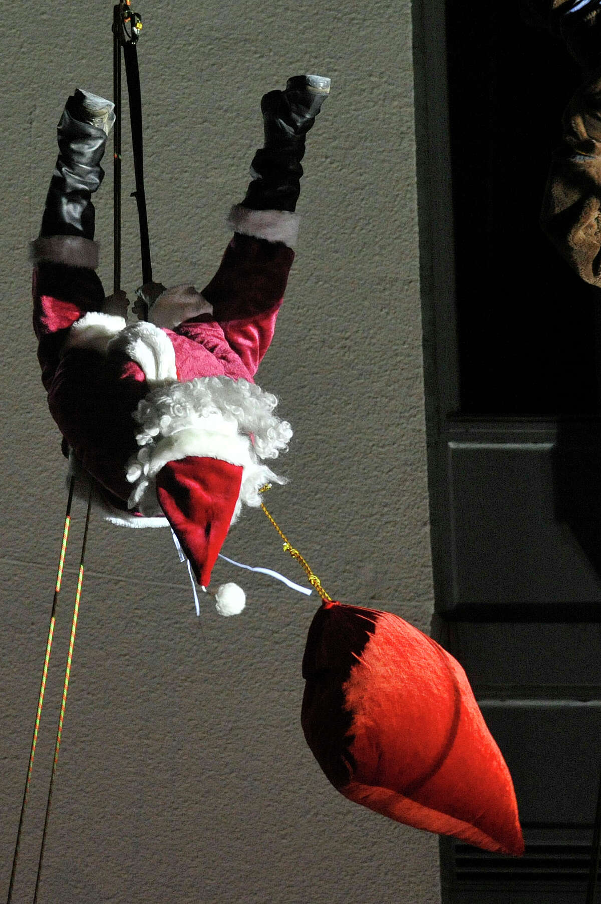 Santa, played by Brian VanOrsdel, hangs upside-down while rappeling down the Landmark Tower during the Heights and Lignts Rappel and Tree Lighting event in downtown Stamford, Conn., on Sunday, Dec. 7, 2014.