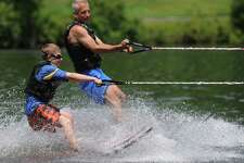 """Noah Schickler, 11, of Ridgefield, goes waterskiing with volunteer Stephen Vonick, of Stratford, at the Leaps of Faith """"Soaring with the Eagles"""" waterskiing day camp for the blind and visually impaired on the Housatonic River in Sandy Hook, Conn. Friday, June 27, 2014.  """"Soaring with the Eagles"""" is a 4-day camp for kids ages six to 17 that teaches waterskiing, wakeboarding and tubing.  Leaps of Faith Adaptive Skiers was founded in 1992 by former waterskiing world champion Joel Zeisler with the goal to build confidence through exposure to recreational and competitve waterskiing for disabled children and adults."""
