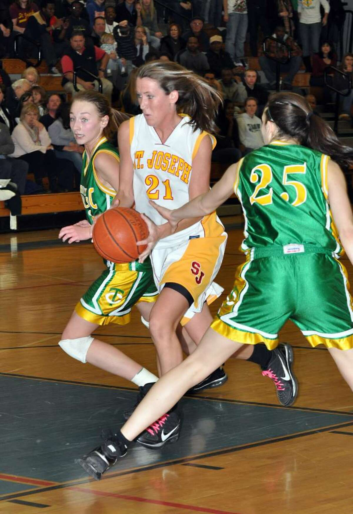 St. Joseph's Michele Gorman breaks through Trinity's defense Machkenzie Griffin and Ali Palma during the first half of the FCIAC girls basketball championship game at Fairfield Ludlowe High School on Saturday, Feb. 27, 2010.