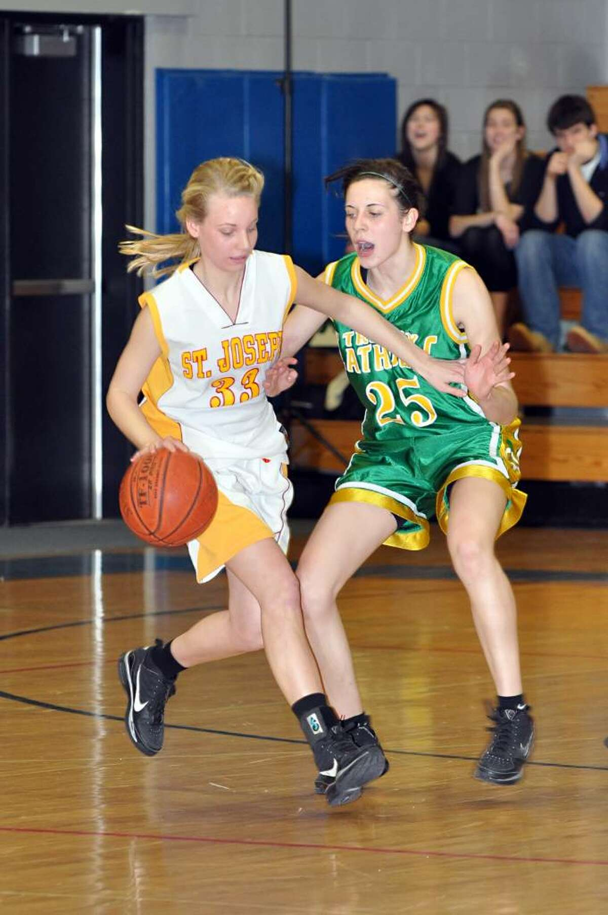 St. Joseph's Alivia Coleman dribbles past Trinity Catholic's Ali Palma during the first half of the FCIAC girls basketball championships at Fairfield Ludlowe High School on Saturday, Feb. 27, 2010.
