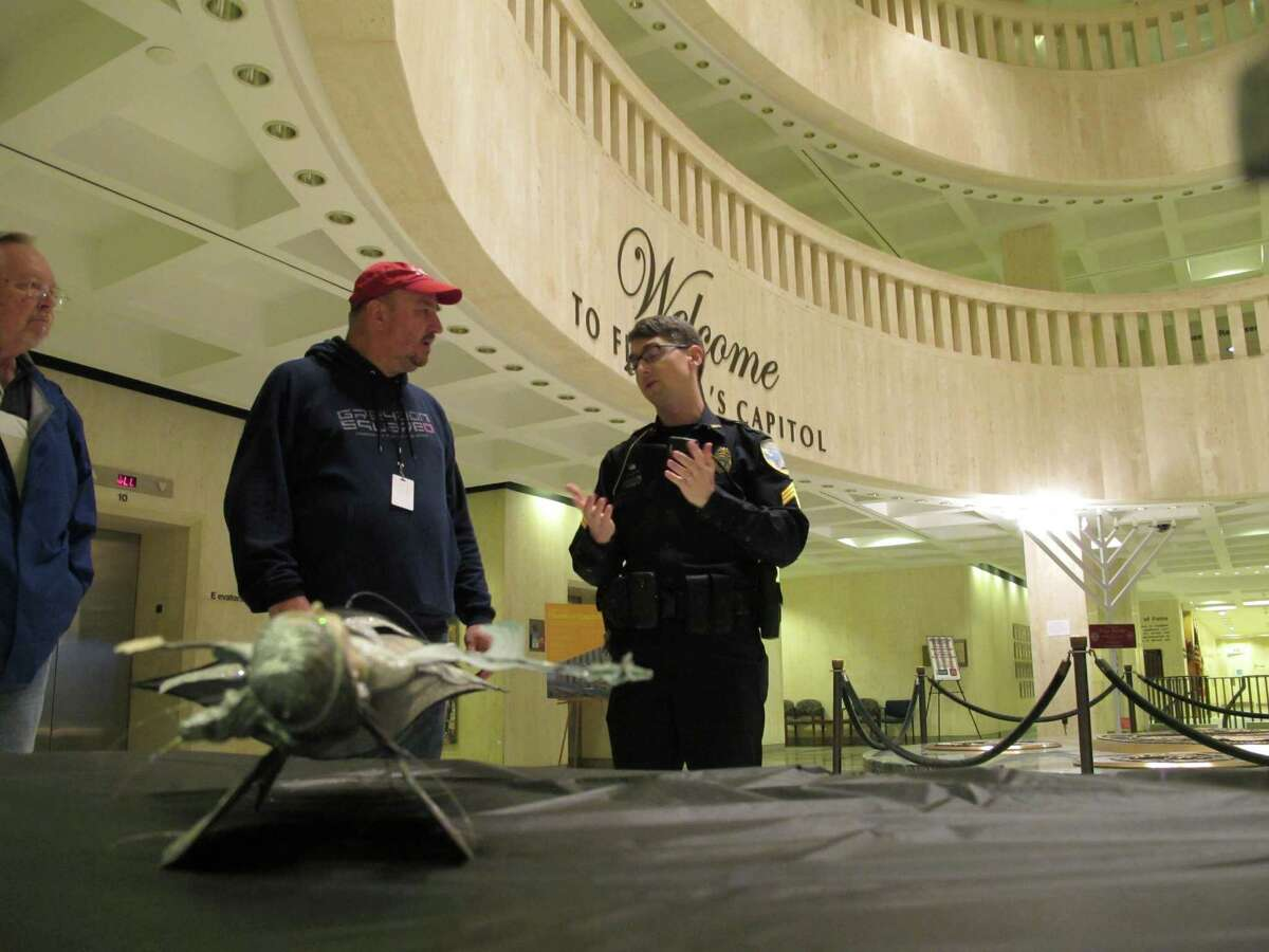 John Porgal, regional director of the American Atheists, second from left, talks with a Capitol Police officer after his Satanic Temple holiday display was damaged in the statehouse rotunda, Tuesday, Dec. 23, 2014, in Tallahassee, Fla.