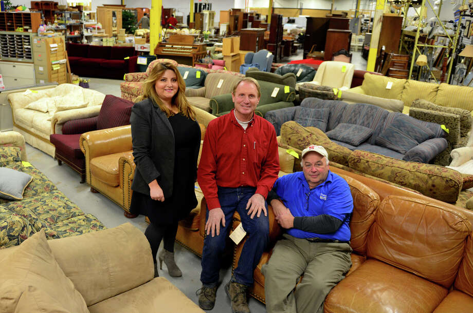 Habitat for Humanity ReStore Procurement Manager Lana Moore, left, poses with Hobbs Inc. supervisor Dave Skelton and ReStore Manager Rich  Desautels, right, at the store in Stratford, Conn., on Thursday Dec. 11, 2014. Habitat for Humanity ReStore accepts furniture through many residential contractors and donations by homeowners who may be upgrading or remodeling. The store then sells items to help fund the building of homes. Photo: Christian Abraham / Connecticut Post