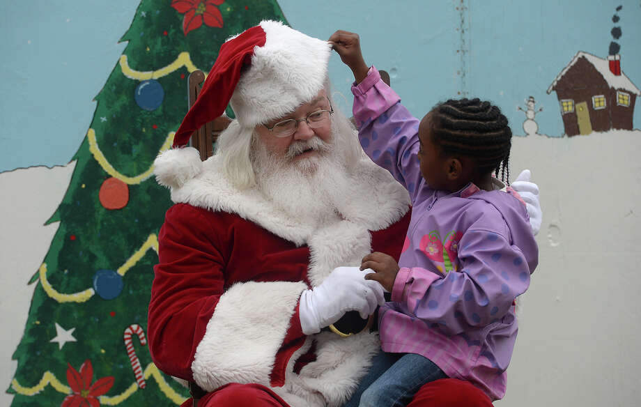 Five-year-old Justice Elia peeks beneath Santa's cap while visiting with him at the Children's Holiday Party and Tree Lighting Ceremony at the Art Museum of Southeast Texas Thursday. Various stations located throughout the grounds offered cookie and ornament decorating, letters to Santa, toys and other holiday treats, as well as a visit with Santa Claus himself.
