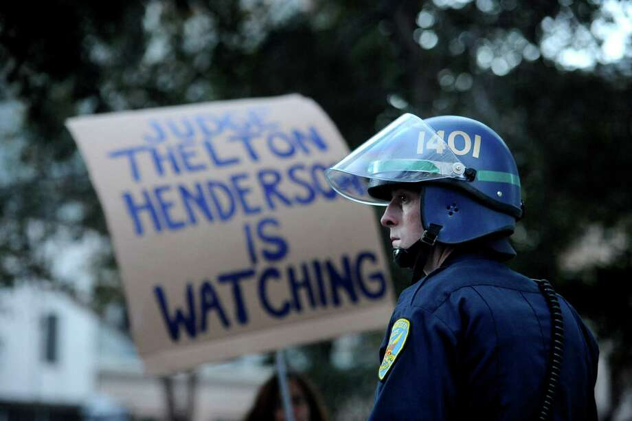 A police officer taking part in a multi-agency raid on Occupy Oakland stands before a protest sign on Monday, Nov. 14, 2011, in Oakland, Calif. U.S. District Judge Thelton Henderson is monitoring Oakland police department reforms in the wake of the Riders corruption scandal. Photo: Noah Berger / Special To The Chronicle / SFC