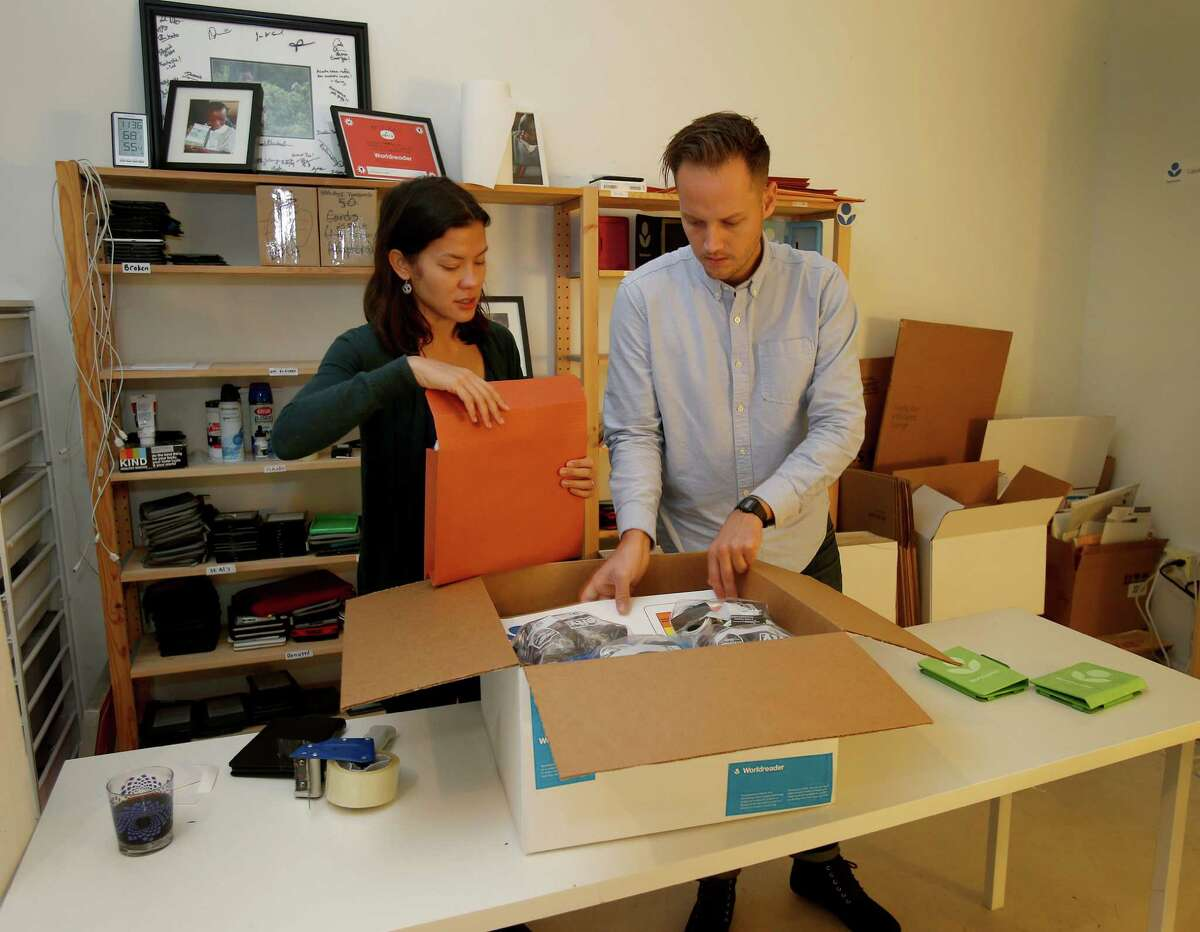 Dani Zacarias (left) and Dan King put together a box full of e-readers, above, to be sent to Tanzania from their San Francisco offices. Grateful students, below, hold up e-readers loaded with book titles from Worldreader.
