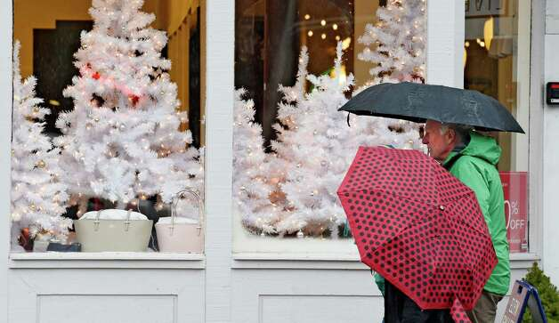 Umbrellas are the accessory of the day instead of snow boots for last minute shoppers on Broadway as warm temperatures and rain have covered the area on Christmas Eve Wednesday afternoon Dec. 24, 2014 in Saratoga Springs, N.Y.   (Skip Dickstein/Times Union) Photo: SKIP DICKSTEIN / 00029981A