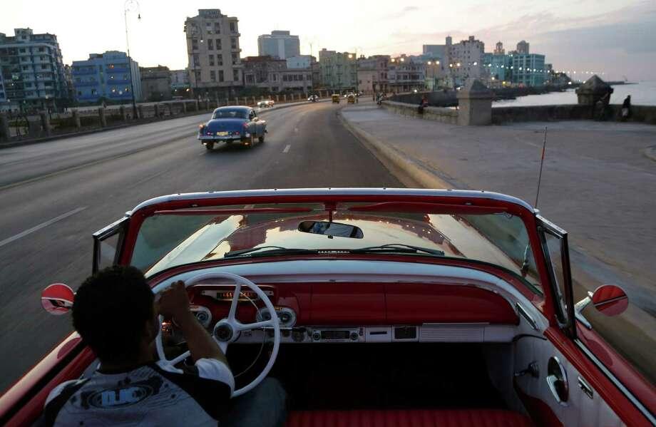 Michel Salgado drives his 1957 Mercury Monterrey convertible car along the waterfront in Havana. Photo: Desmond Boylan / Associated Press / AP