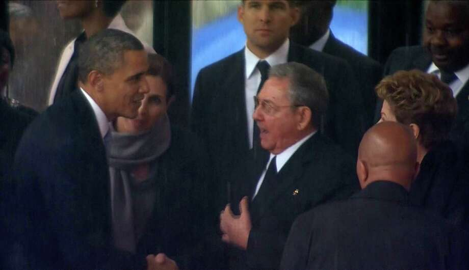 President Barack Obama shakes hands with his Cuban counterpart, Raul Castro, in Soweto, South Africa, for the memorial service for former South African President Nelson Mandela last year. Our readers comment on the thawing of dilomatic relations between the U.S. and Cuba. Photo: The Associated Press / pool sabc