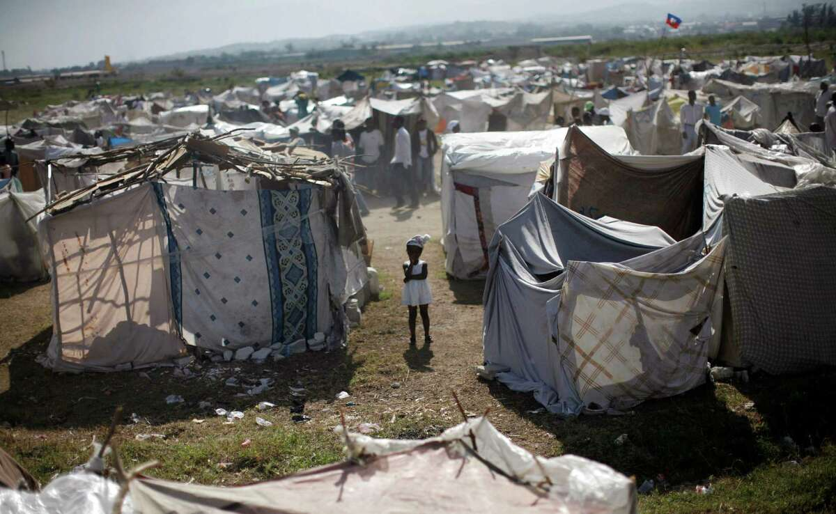 In this 2010 photo, a child stands among makeshift tents at a refugee camp for Haiti quake survivors.