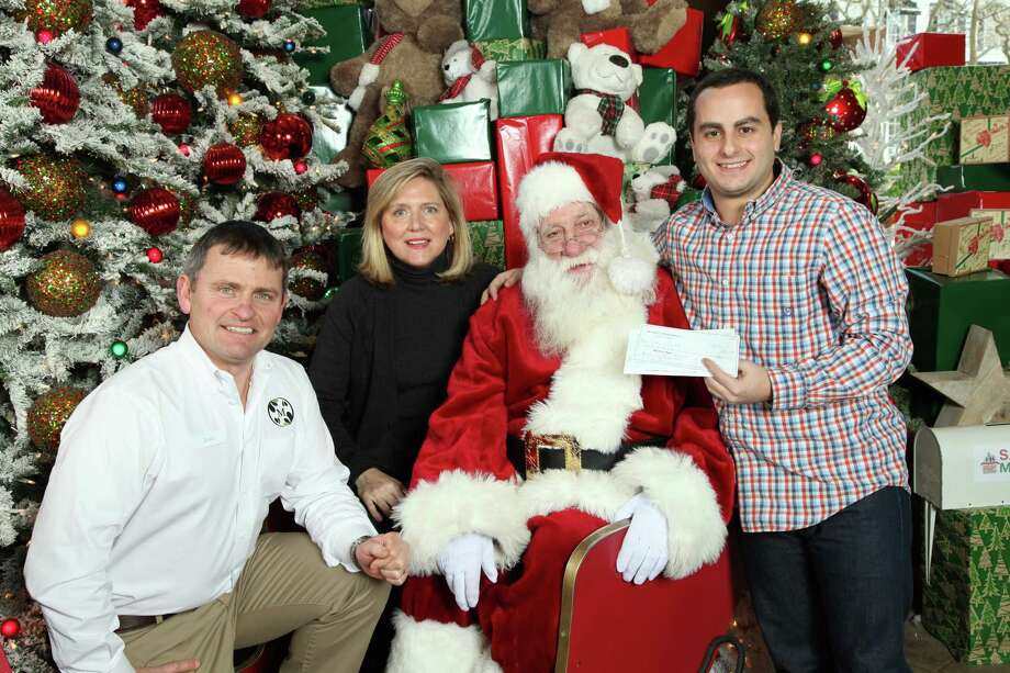 The season of giving continued in earnest at McArdle's Florist and Garden Center in Greenwich, Conn., in the past several weeks. On a recent visit, Branden Hahn of Kids in Crisis, right, stopped by to visit Santa and accept a donation of $2,465 from James McArdle of McArdleís, left, and Tammi Ketler of TMK Sports & Entertainment, producer of the sixth annual Greenwich Reindeer Festival and Santaís Workshop and Greenwich Holiday Stroll. Money was raised during the stroll, held Dec. 6 and 7, 2014, with $5 from every photo taken with Santa, as well as every wreath purchased, going toward the nonprofit organization. A Kids in Crisis Giving Tree will remain at McArdleís through Dec. 24. Photo: Contributed Photo / Stamford Advocate Contributed photo