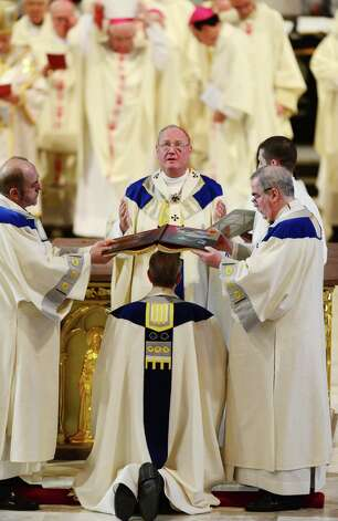 Monsignor Edward B. Scharfenberger is installed as Bishop of the Albany Diocese by Cardinal Timothy Dolan, Archbishop of New York, center, during an ordination ceremony Thursday, April 10, 2014, at the Cathedral of Immaculate Conception in Albany, N.Y. (Will Waldron/Times Union) Photo: WW / 00026421C