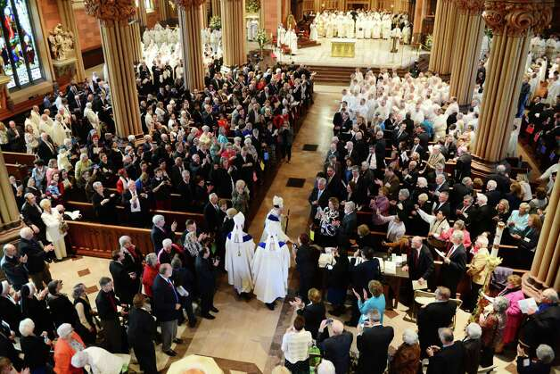 Bishop Edward B. Scharfenberger gestures to the crowd following his ordination ceremony Thursday, April 10, 2014, at the Cathedral of Immaculate Conception in Albany, N.Y. Scharfenberger was ordained as Bishop of the Albany Diocese by Cardinal Timothy Dolan, Archbishop of New York. Former Albany Bishop Howard Hubbard is pictured left. (Will Waldron/Times Union) Photo: WW / 00026421C